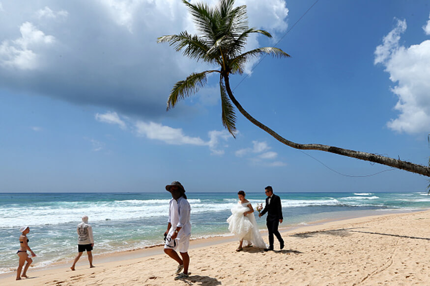 Tourists dressed in wedding clothing walk along Habaraduwa Beach in Galle